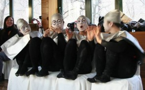 Scene from a Hua Dan Consulting Programme performance: four mimes perched on top of a table