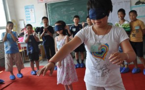 Two blindfolded children taking part in a Hua Dan Children's Programme activity, with their classmates cheering them on