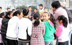 A group of children huddled in a circle as part of a Hua Dan activity in the Sichuan earthquake area; one girl has turned around to pose for the camera